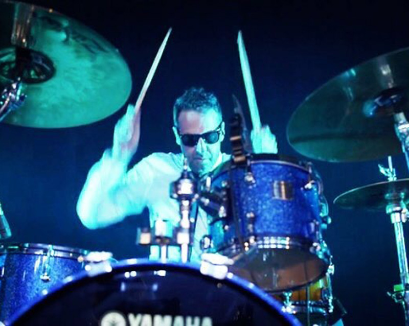 photo of Brent Berry wearing sunglasses and playing a drumset on stage, blue lighting