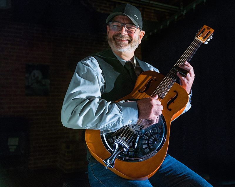photo of Danny Hargis holding a guitar smiling at the camera
