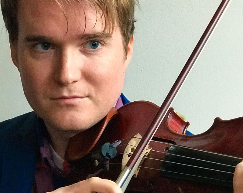 close up of Patrick Conlon posing with his violin
