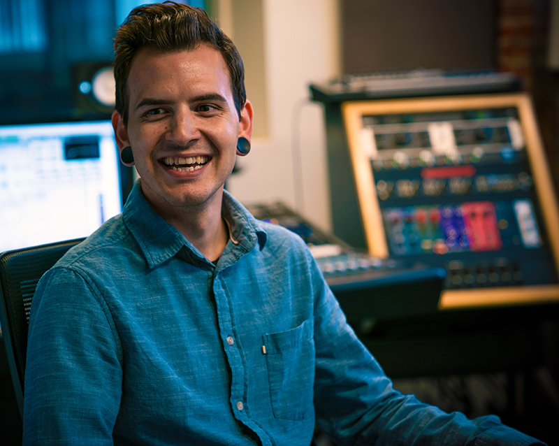 photo of Rob Derrick sitting in front of recording equipment looking off to the left.