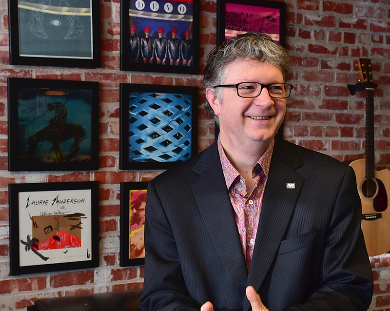 photo of Scott Booker smiling looking to the right while standing in front of framed records and guitars hanging on a brick wall