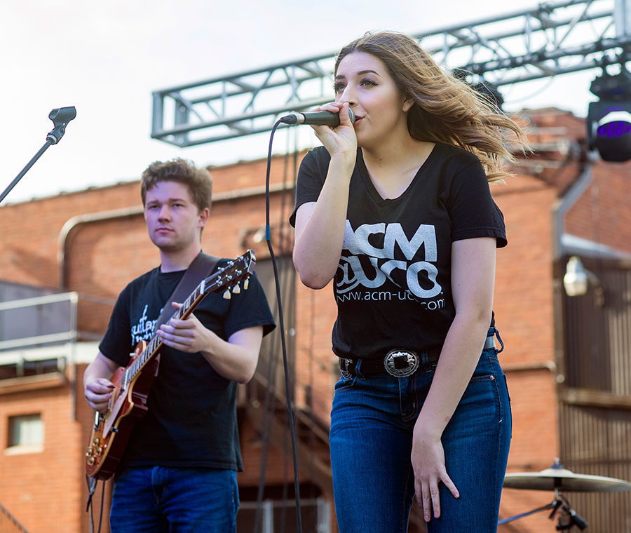 photo of a girl singing and a guy playing guitar on an outdoor stage in Bricktown during Metro Music Fest